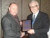Wayne Bingle (r) accepts a lifetime service award from John Hammill, CIPH chairman of the board.