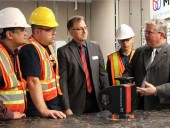 Grundfos Canada president Simon Feddema (r) explains the workings of the company's high-efficient MAGNA3 circular pump to KPU plumbing students Ravinder Walia, Richard Baziuk and Aws Elmakayed while plumbing instructor Sven Rohde observes.