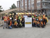 Joe Di Ilio, president, Stanley Black & Decker Canada (centre left) and Liz Etsell (centre right), volunteer site coordinator for Habitat for Humanity GTA, with the Dewalt participants in the Habitat for Humanity Adopt-a-Day Challenge GTA.