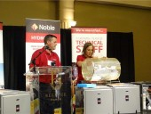 Tom Breen, Noble HVAC Sales Manager - Toronto Region prepares to announce the winners of the prize draw while Ulyana Fedyna, Noble marketing manager, HVAC & Hydronics, spins the drum.
