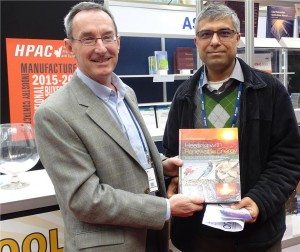John Siegenthaler (l), author of Heating With Renewable Energy, presents a copy of the book to Joydeep Bose of EB Air Control Inc. on the final day of the CMPX show.